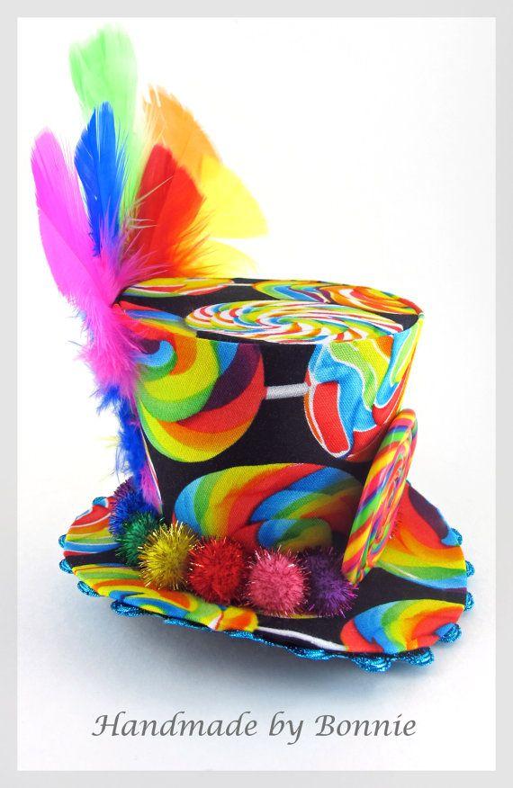 Costumbre el listado según lo discutido con el cliente. Tela base sigue siendo la misma.  Este pequeño sombrero de Copa se cubre con diversión dulces del arco iris! Completo con un alboroto de plumas de colores en la parte trasera y una piruleta hecha a mano en la frente. Un anillo de pompones brillantes arco iris rodea el borde. Mide aprox 4 de alto y 5 de ancho en la base. ¡Super divertido y coloridos accesorios! Apoyo excelente foto. Se conecta fácilmente a una diadema de su elección (no…