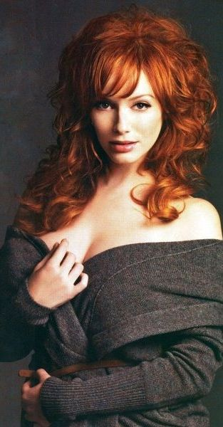Christina Hendricks posing for a standard portrait shot, but with an seductive expression on her face and a little classy teasing with her right hand near her chest.