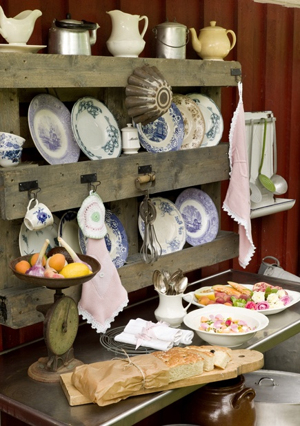 A vintage kitchen re-purposing a wood palette for storage and display.