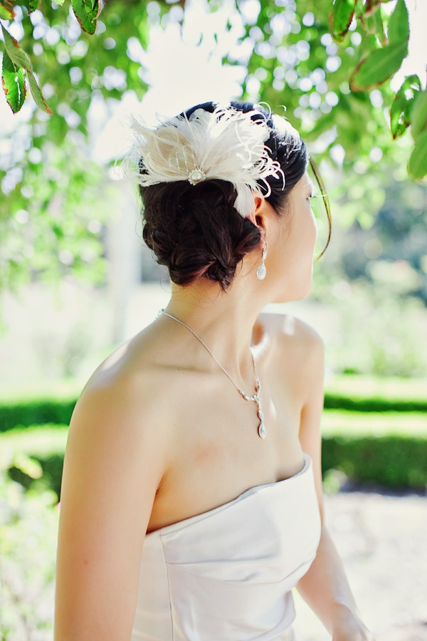 Wedding up-do with a simple feather hair accessory.