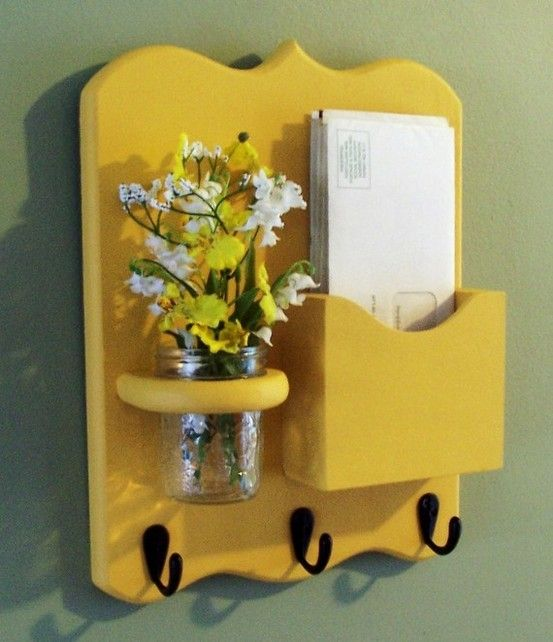 thrift store mail sorter find painted in sunny yellow with hooks added.