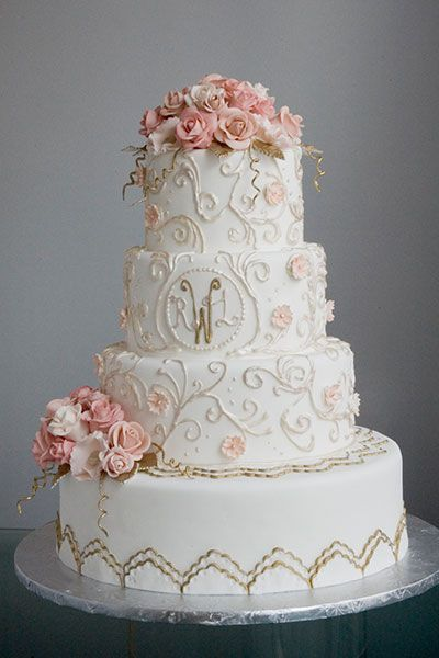 Delicate flowers, romantic swirls, metallic accents, and a sweet monogram come together beautifully in this lovely cake
