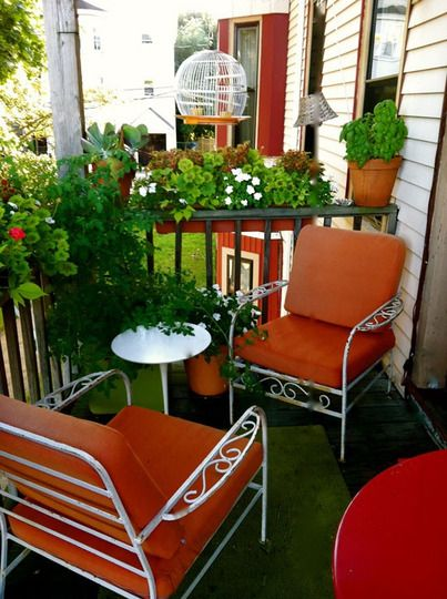 love this apt balcony-the greenery is great and the intimate seating, the green and red-orange table and chair cushions really make it pop!
