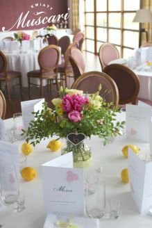 Żółto różowe bukiety na stołach gości weselnych