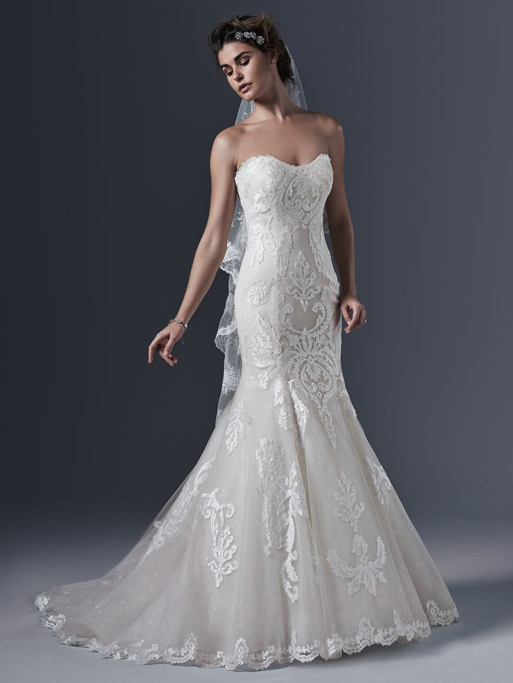 Sottero and Midgley - LOVAI, Timeless romance is updated in this classic mermaid silhouette. Striking bold patterned lace on tulle cascades down the bodice and traces the hemline. A layer of glitter tulle adds a subtle hint of sparkle. Finished with delicate scoop neckline and crystal buttons over zipper and inner corset closure.