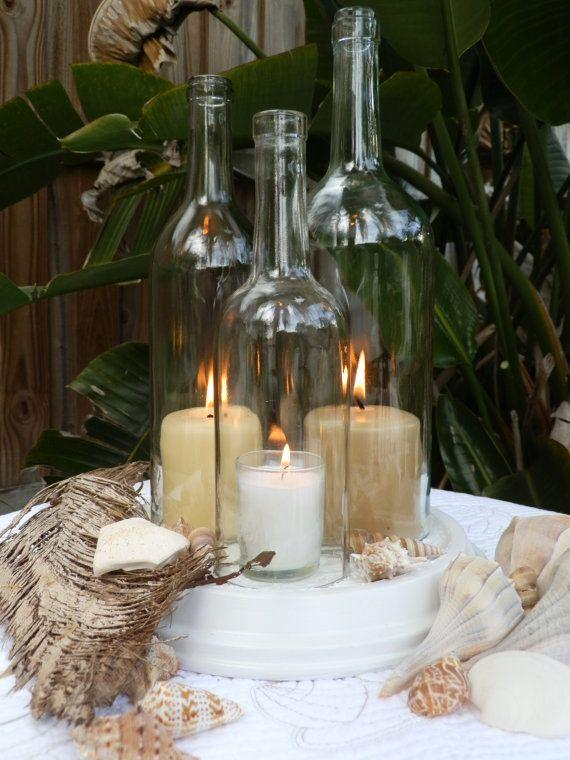 Hermosa botella de vino centro de mesa de lámpara de huracán de arte.  Tres reciclan botellas de vino de diferentes tamaños y alturas. Un 1.5 litros claro en 12 Una de 750 ml. claro en 10,75 Una de 750 ml. claro en 9,75  Mano cortada y meticulosamente pulida a un borde super suave.  Base de arcilla incluyen está pintado de blanco y diseñado con un patrón de remolino con textura para permitir el flujo de aire así que velas puede respirar. La base es de 10,75 pulgadas de diámetro.  Excelente…