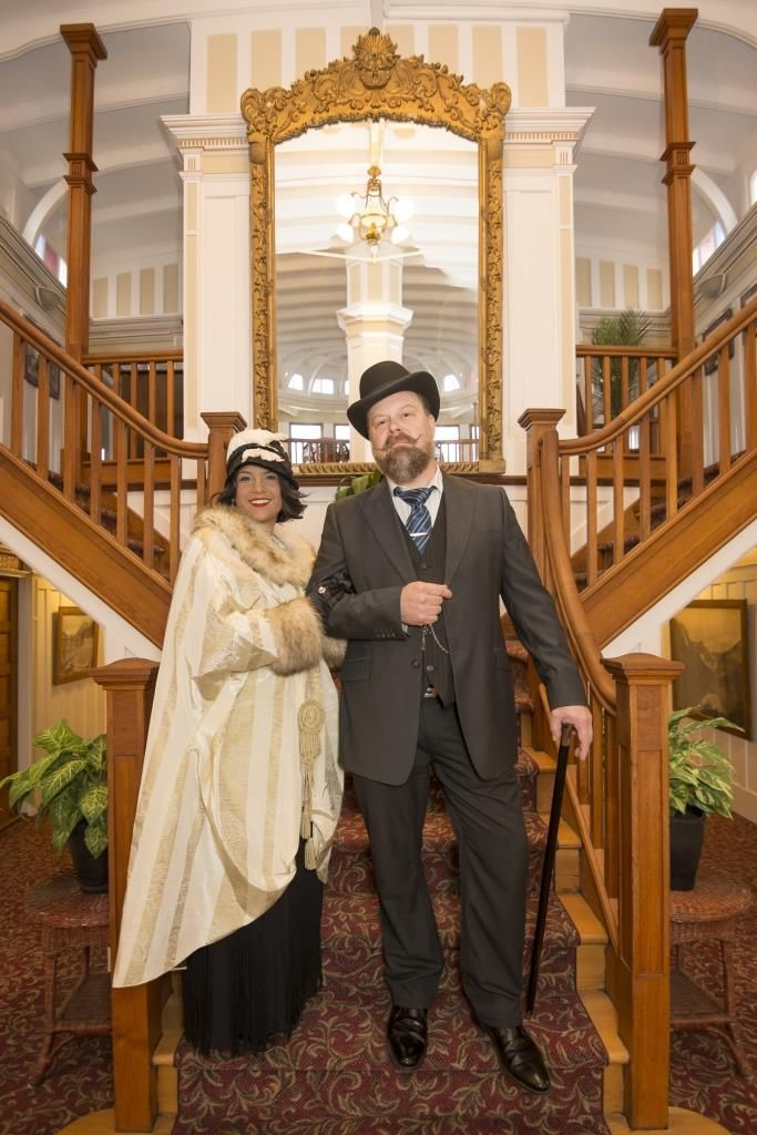 Yanti (Vocalist and Songwriter) stands in vintage costume with Tim Tweed (DJ) in front of the grand stair case at the SS Sicamous (in Penticton BC).  Photos were taken by Callium Smith, a photographer based in Naramata BC.