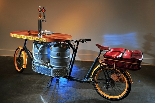The Beer Bike is a custom-built cargo bicycle that features two beer kegs, a wooden bar wi...