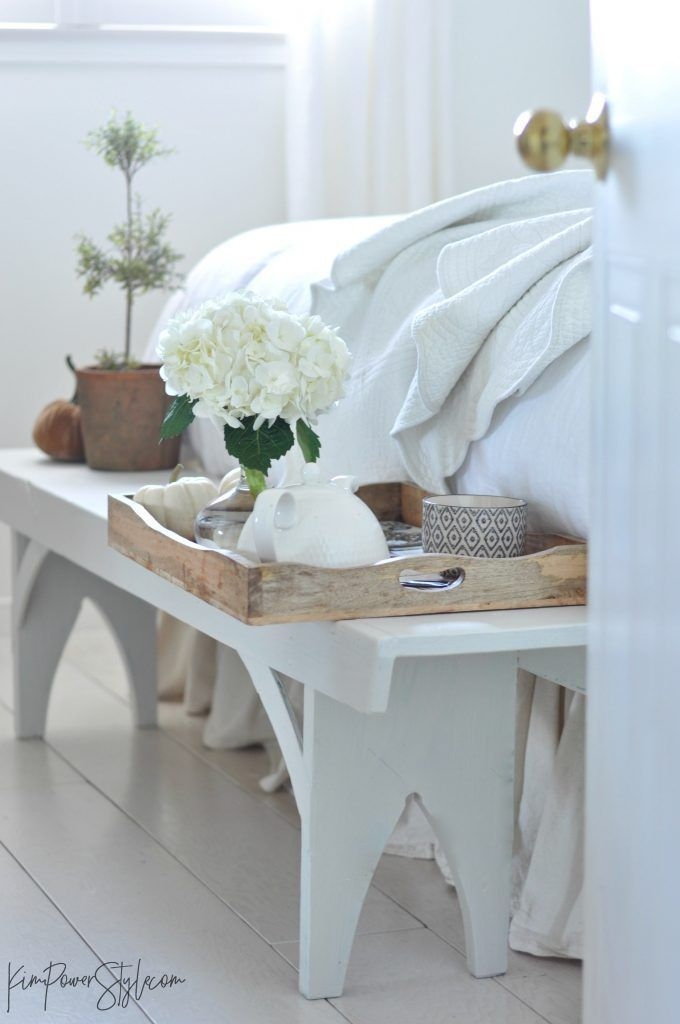 A wooden tray with a pot of tea and a few little fall touches | bench at the foot of the bed