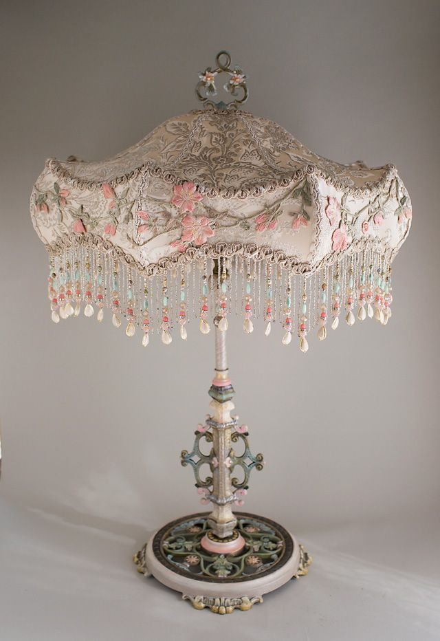 Antique large scale table lamp with flowers has been hand painted and holds an Ivory Carousel silk lampshade. The shade is covered in a luxurious Edwardian era ivory silk satin with silver woven through it. This was from an antique wedding gown and is overlaid around the edge with antique embroidery in pinks and greens. This a a romantic, feminine lamp and lights up beautifully. A jeweled pull chain turns the lamp on and off. Overall height is 32 inches to the top of the finial. The shade is…