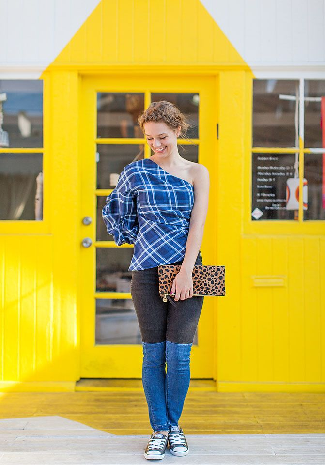 Blogger Bella Bucchiotti of xoxoBella is wearing Blank Denim two tone jeans, a Petersyn Tilly blouse, a Rebecca Minkoff clutch and metallic converse in Venice, California.
