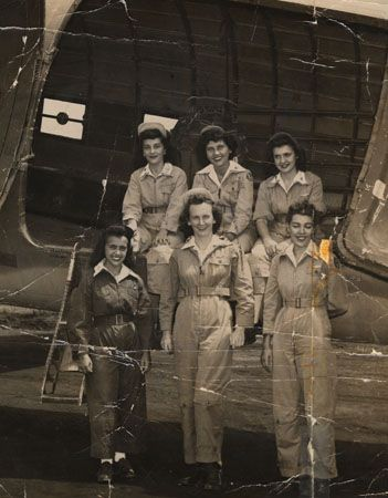 Six flight nurses from the 801st medical air evacuation transport squadron pose in an open airplane bay, circa 1944. All are wearing flight uniform coveralls. Pictured (clockwise from top-right) are: Terry Terrance, Loretta Ruggerio, Helen Hunter Weant, Kitty Lapan, unknown, and Cora Deffebaugh ~