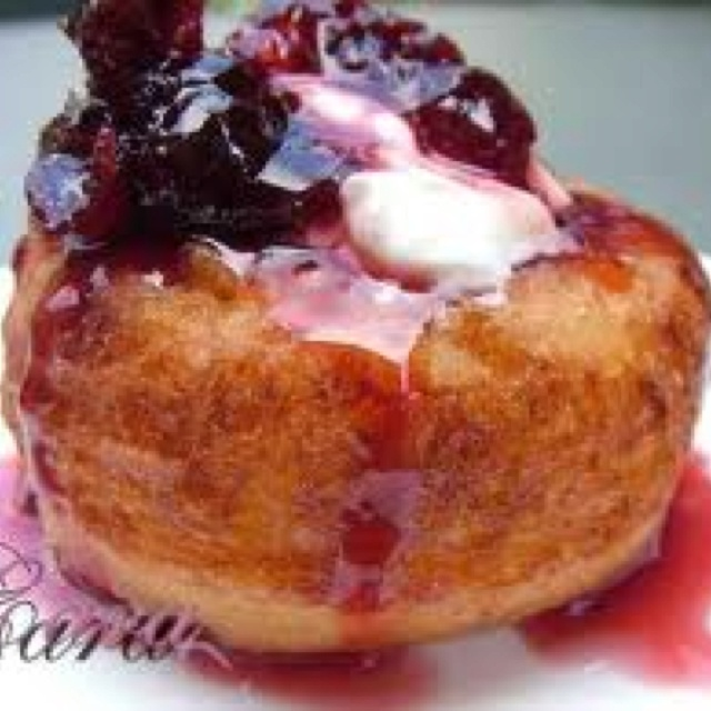 Romanian dessert. Papanasi-made from a mixture of sweet cheese, eggs, and semolina, boiled or fried and served with fruit syrup or jam and sour cream