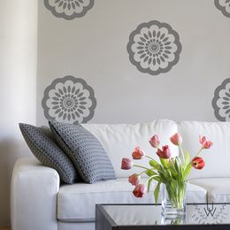 Floral wall pattern decals in grey is shown on a light beige wall behind a modern white couch and a coffee table with red tulips in a vase on top. Each floral decal features a flower-like look and variety of patterns in a circular encapsulation.