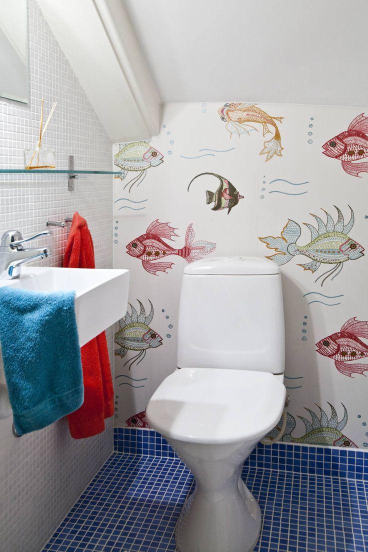 Värikkäät kalat uiskentelevat Nina Campbellin Aquarium-tapetissa. Pesuallas ostettiin Stockmannin Hulluilta Päiviltä. Sininen mosaiikkilaatta on Laattapisteen. Lasihylly, peili ja koukut ostettiin Ikeasta.