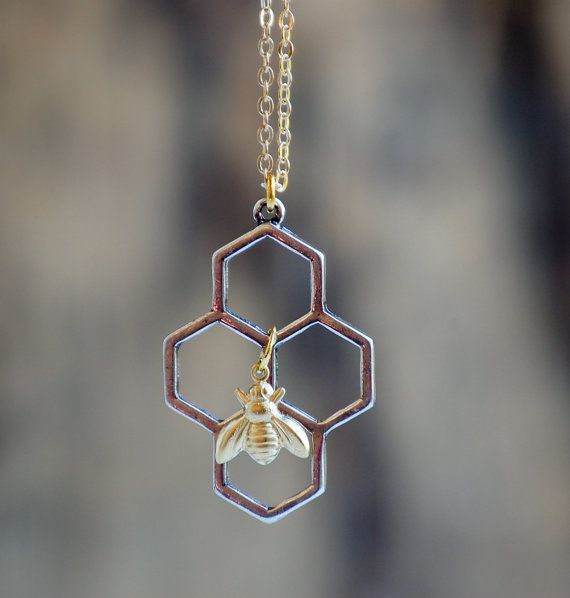 Un fascino a nido dape è il fuoco per questa Collana geometrica. Questa natura ispirato geometrica a nido dape ha una piccola ape mellifica ottone crudo dorato. Favo pende dalla vostra scelta di una catena in ottone dorato o una delicata catena piena doro. Il fascino del pettine di miele misura circa 1 1/8 pollici di altezza.  La tua collana arriverà accuratamente avvolto in un sacchetto di cotone beige con coulisse. Perfetto per dare del regalo. Questa borsa di gioielli può essere…