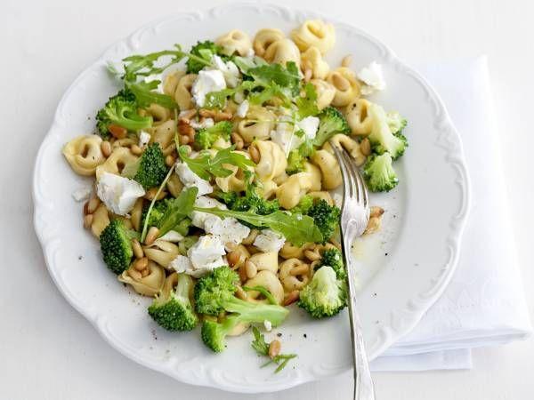 Kook de tortellini in ruim water met zout in 15 min. beetgaar.  Kook de broccoli in 6 min. beetgaar.  Rooster in een droge koekenpan de pijnboompitten goudbruin en schud ze op een bord. Giet de tortellini en de broccoli af en schep op 4 borden.   Verdeel er de rucola, de geitenkaas en de pijnboompitten over. Besprenkel met de olijfolie en bestrooi met zout en peper naar smaak.  Aantal kcal: ca. 507 p.p.