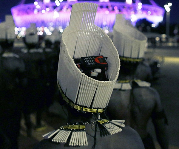 A performer with an electronic headdress waits to enter the Olympic Stadium during the Closing Ceremony of the 2012 Summer Olympics, Sunday, Aug. 12, 2012, in London. (AP Photo/Julie Jacobson)