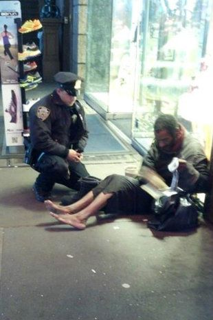 A photo of a New York City police officer kneeling down to