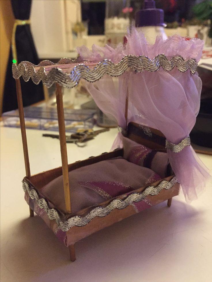 Dukkehus seng til en lille prinsesse. Lavet af en kattemadsboks, træ grillspyd, lidt maling og en stofrest.