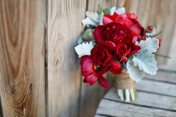 Winter wedding bouquet of Red peony, red roses, red ranunculus, red tulips, red amarylis, red spray roses, red berry, and silver dusty miller. The bouquet is wrapped with twine; from http://thefullbouquetblog.com/