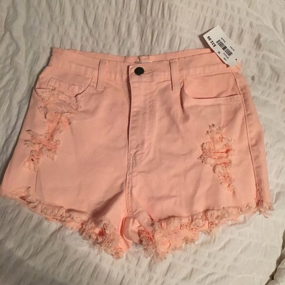 Ripped peach shorts NWT Stretchy denim peach/pink colored shorts from mystique never worn new with tag frayed bottom and ripped up look in front Shorts Jean Shorts