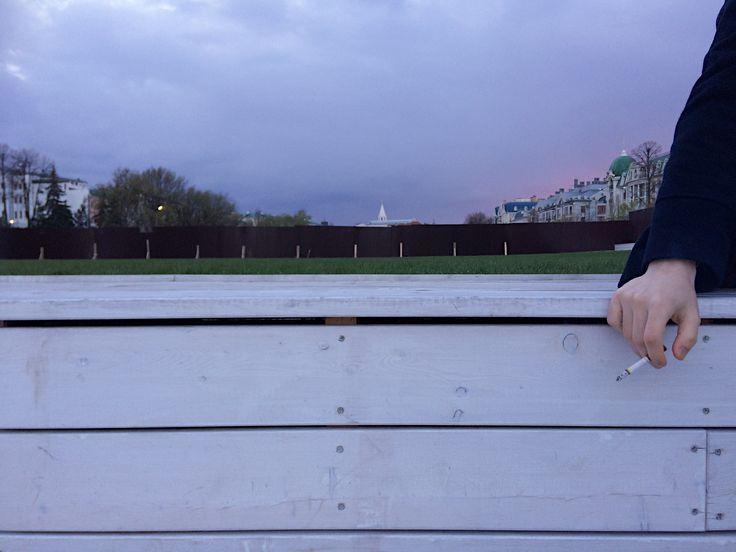 Закатный градиент фиолетово-сиреневый, деревянная светлая  скамья и ненавязчиво свисающая рука с сигаретой. На фоне свежая зелёная трава, казанский кремль и старинные дома.