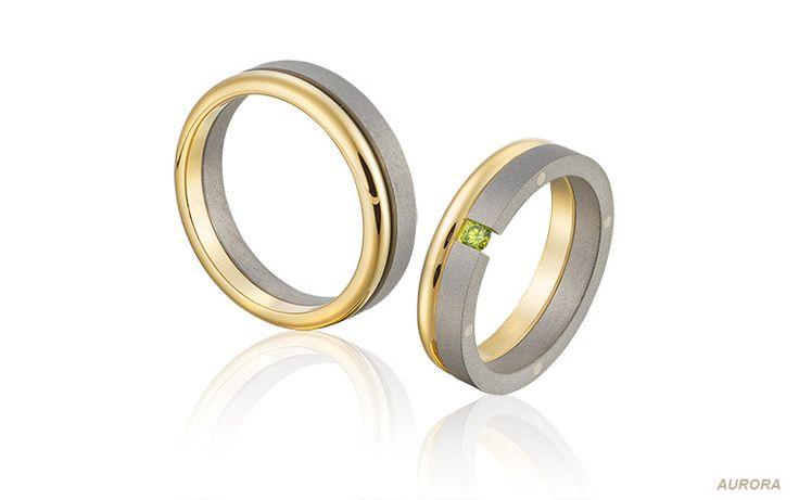 Unieke trouwringen van titanium en geelgoud, bezet met een fonkelende heldergroene briljant.
