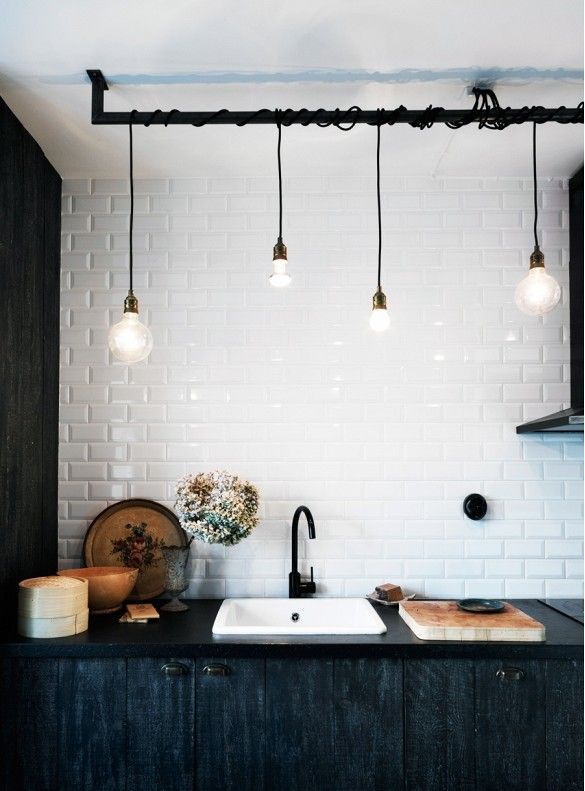 This kitchen features industrial elements like hanging cord lights and a vintage charm antique decor and brushed wood cabinets