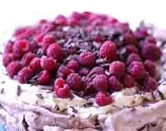 A deliciously decadent twist on an old favourite. This chocolate pavlova is topped with raspberries and cream.