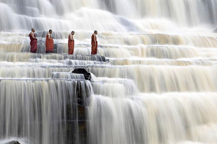 Buddhist monks at Pongour Falls, the largest waterfall in Dalat, Vietnam.    Photographer Dang Ngo