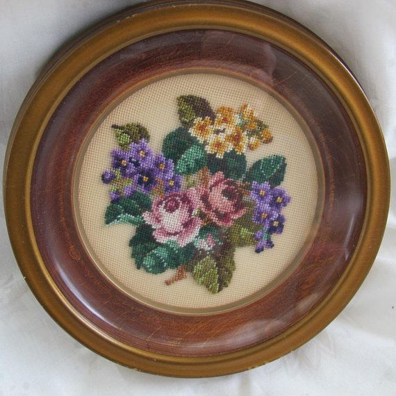 Delightful petit point picture featuring a bouquet of pink roses, purple and peach violets. Round wood frame with glass that is offset from the needlework. Overall diameter is 7 inches. Frame is about 1 inch deep. Needlework is about 4 1/4 inches in diameter. Original frame, paper