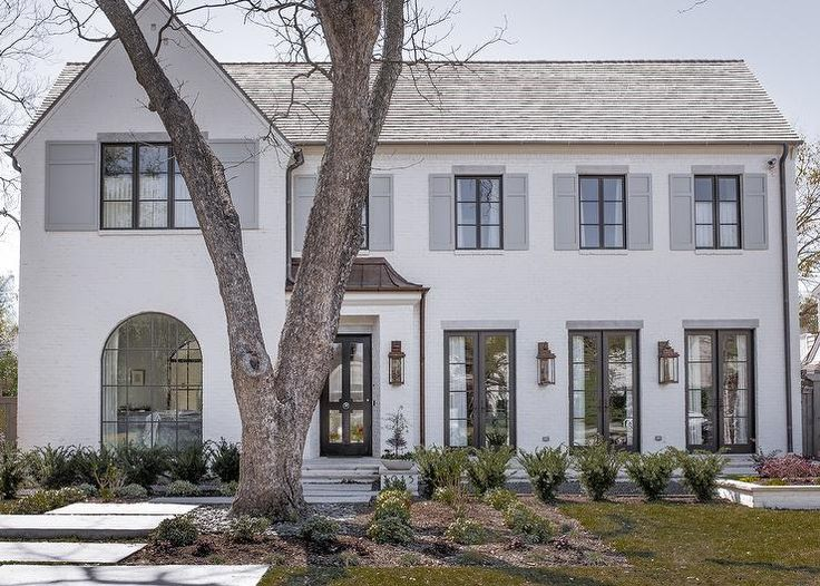 White and gray home features a white painted brick exterior accented with windows finished with dove gray shutters.