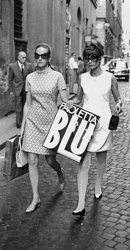 Doris Kleiner (Yul Brynner's former wife) photographed with Audrey Hepburn Dotti (in Givenchy dress, stockings and handbag, Oliver Goldsmith sunglasses and René Mancini shoes) by Elio Sorci during their shopping (on Via Condotti) in Rome, June 1969.