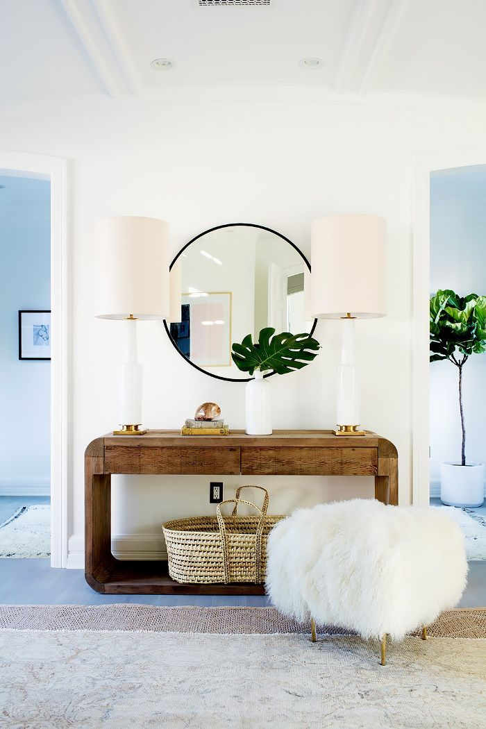 In this space, accents like white, ceramic lamps, a mohair throw, and woven jute rug cultivate vintage glamour vibes.