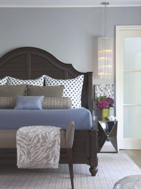 polka dot bedding with neutral and blue bedding. mirrored side table.