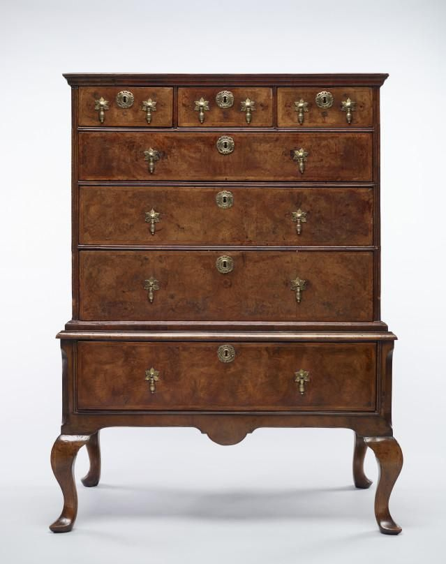 Walnut veener chest on stand, with seven drawers, made in England about 1700. The chest has three long drawers and three small drawers each with original brass keyhole escutcheons and drop handles. The top and drawers are decorated with herringbone or feather edging outlined with double cock beading. The stand has one deep drawer with matching keyhole escutcheons and handles with inverted dome decoration on apron. The massive plain cabriole legs have pointed club feet.
