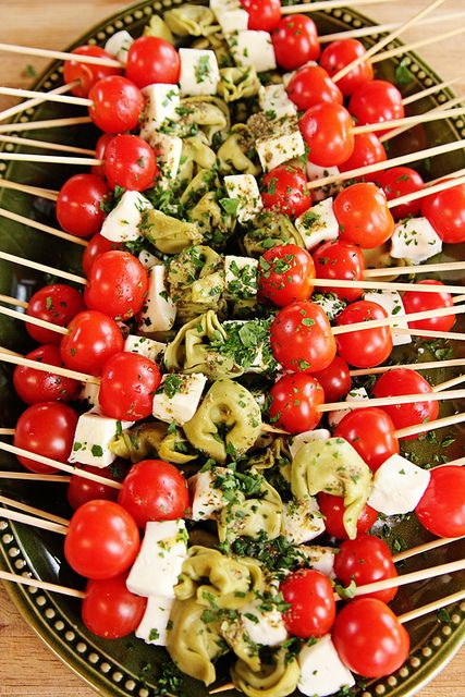 Tons of party food ideas, including these gorgeous skewers --> cherry tomatoes, chunks of fresh mozzarella and cooked spinach tortellini topped with pesto dressing via The Pioneer Woman #party #appetizer