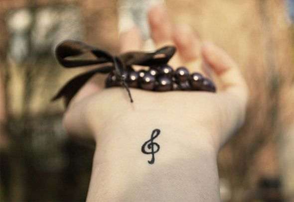 small treble clef wrist tattoo design idea