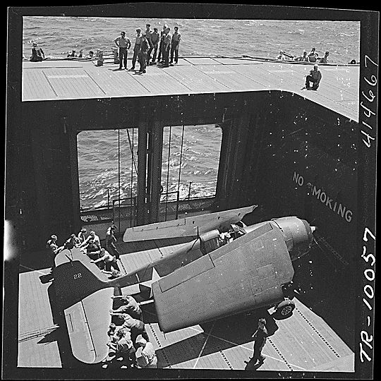 Grumman F6F Hellcat. Navy crewmen aboard the USS Monterey (CVL-26) bringing an F6F to the flight deck on an elevator.  (Photo: National Archives and Records Administration)