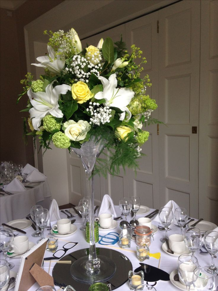 Martini vase centrepiece Wedding. Lemons, greens and white. Lilies, Roses and Viburnum.