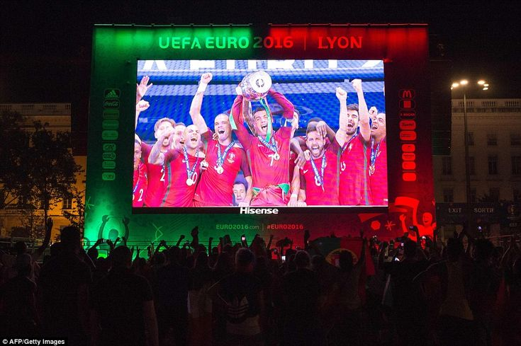 On the screen in the Lyon fan zone Cristiano Ronaldo lifts the trophy as Portugal supporte...