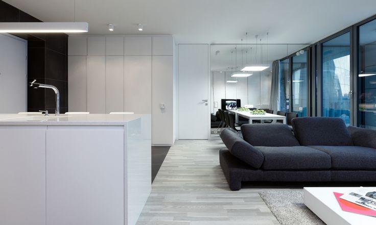 Pre zachovanie elegancie centrálneho priestoru, ktorý obsahuje vstupný, kuchynský, jedálenský aj obývací priestor sme jednotlivé kusy nábytku navrhli v rovnakom štýle.  Skriňa v predizbe, kuchynská zostava, dvere do spálni aj obklad steny za televízorom sme preto navrhli z rovnakého materiálu - bieleho matného laku.
