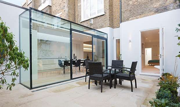 very economically designed extension to a basement flat doesnt block off the light to rear rooms, but provides a very light kitchen diner with patio to the rear
