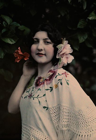 A Spanish woman with flowers in her hair posing in Tampa, Florida, in 1929.   Photo by Clifton Adams.