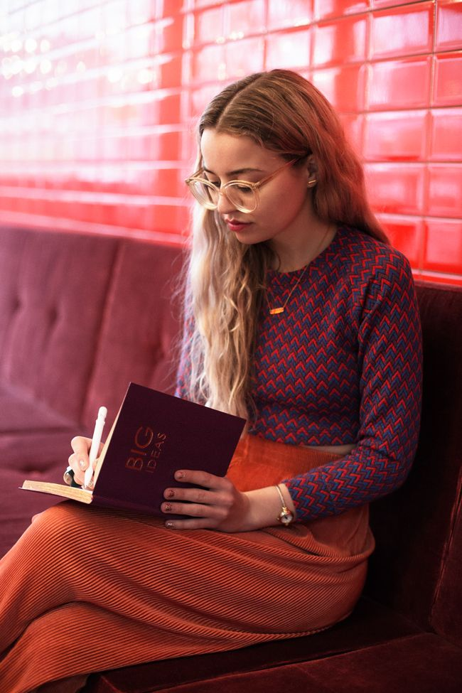 A geeky look you can pull off. Oversized glasses, a structured top and a long orange skirt.