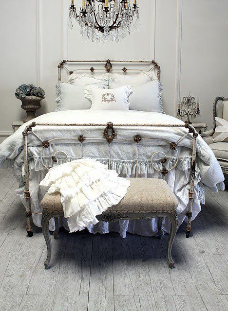 White iron and brass ornate vintage bed, white duvet, ruffle, and pillows, ornate bench with neutral cover and tacks, beautiful chandelier