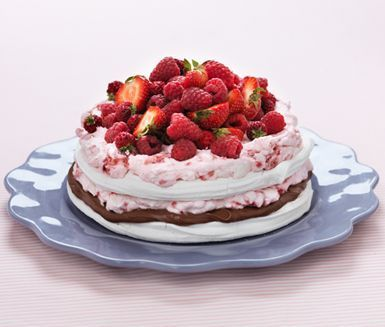 En helt underbar, lyxig marängtårta som kommer bli högt uppskattad av stora och små! Fördela din lena mjölkchokladtryffel och söta hallongrädde på krispiga marängbottnar. Servera tårtan med ett gäng söta, färska jordgubbar och några hallon på toppen.
