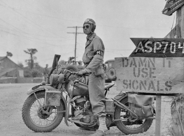 """American MP and ubiquitous Harley Davidson photographed on July 20, 1944. Note the scabbard for the M1A carbine in front of right-side handlebar and the road sign urging drivers to """"Damn it, USE SIGNALS""""."""