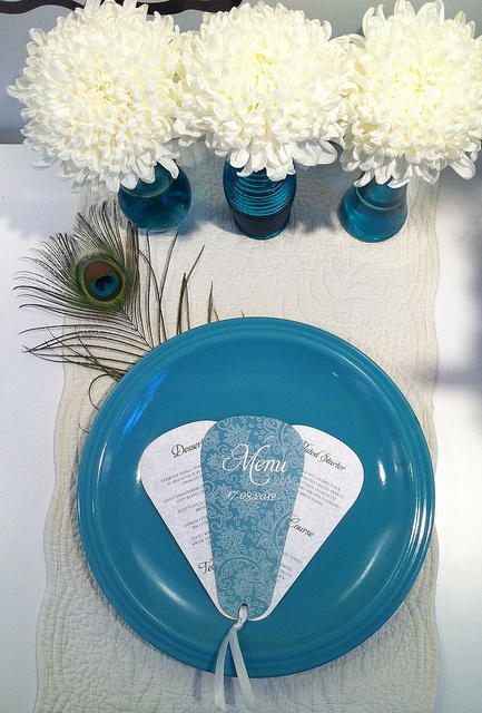 A menu fanned on a plate with a pretty blue cover.    www.facebook.com/RubyGreyCreative